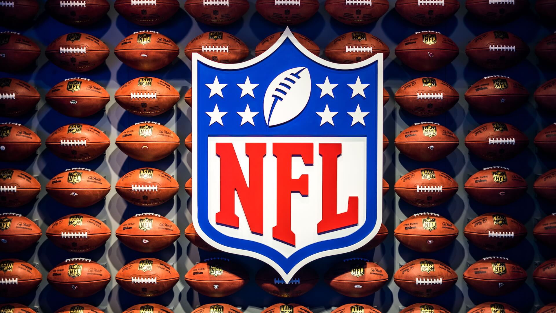 NFL logo with footballs in the background